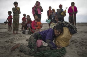 An elderly Rohingya woman collapses, after the wooden boat she and her companions were travelling on from Myanmar crashed into the shore, in Dakhinpara, Bangladesh.