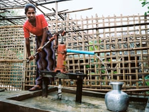 A Rohingya girl pumps water at a camp reliant on communal wells