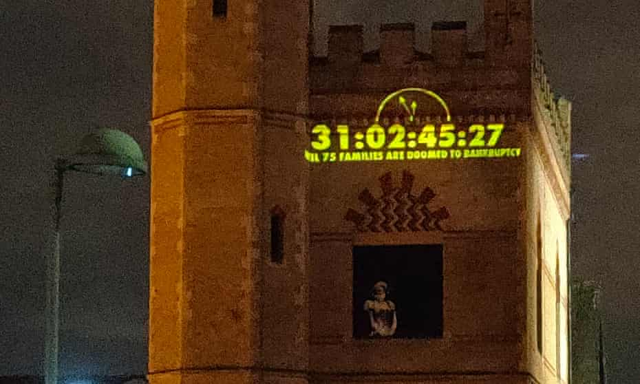 """The Bridge House residents' """"doomsday clock"""", counting down the time until the government funding deadline, is projected on to a neighbouring building."""
