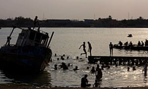 People swim in the Shatt al-Arab waterway in Basra to beat the heat