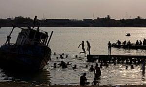 People swim in the Shatt al-Arab waterway in Basra to beat the heat