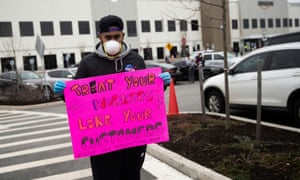 Jordan Flowers holds a sign at an Amazon building in Staten Island, New York, on 30 March.