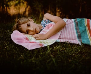 A young girl laying on the grass