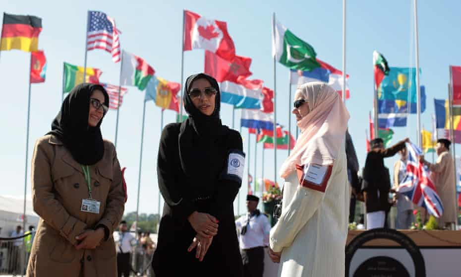 Women attendees in front of flags from many countries at the UK's largest Muslim convention, Jalsa Salana