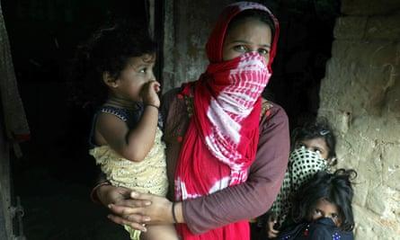 Seorang wanita dan anak-anak menunggu skrining TB di desa Jakhada, India utara.