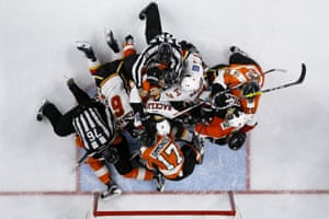 Referees try to break up a fight between the Philadelphia Flyers and the Calgary Flames.