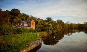 An autumn landscape featuring a large brick house on the banks of the River Weaver in Northwich, Cheshire.