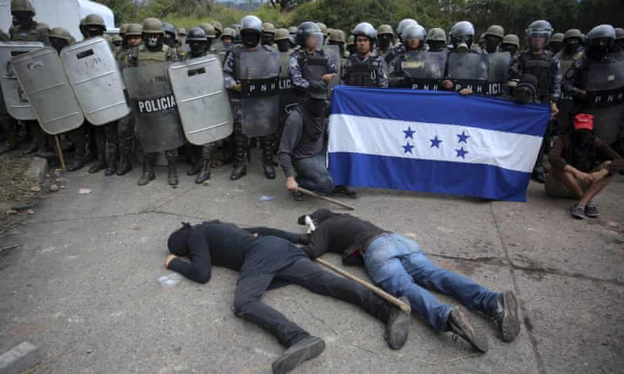 Opposition supporters stage a die-in in front of a police and military checkpoint where they demonstrate, in Tegucigalpa, Honduras, on 22 December 2017.