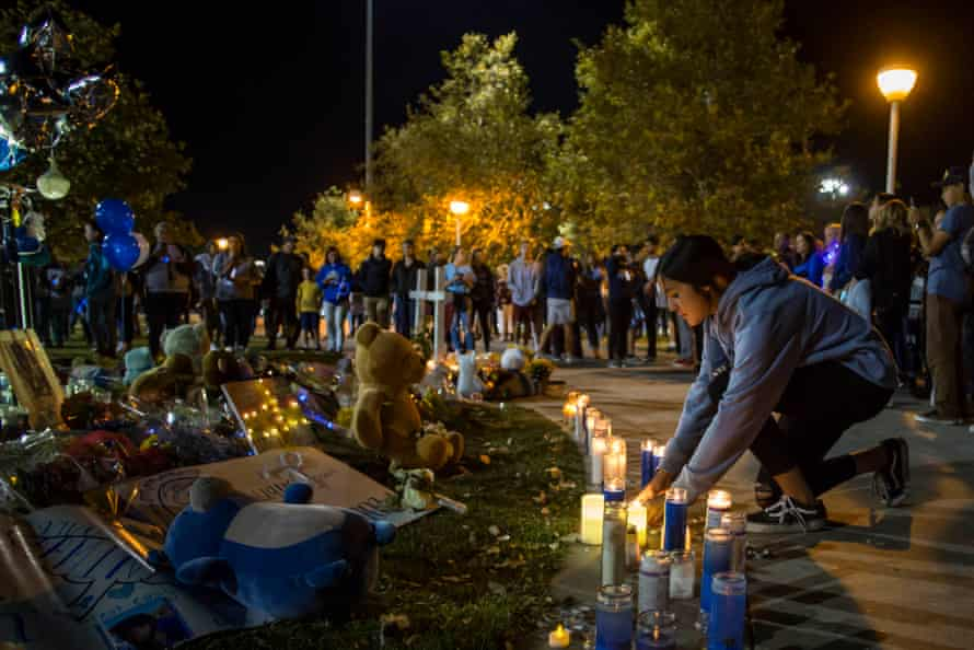 Andrea Tovar lights a candle at a vigil held for shooting victims on Sunday in Santa Clarita, California.