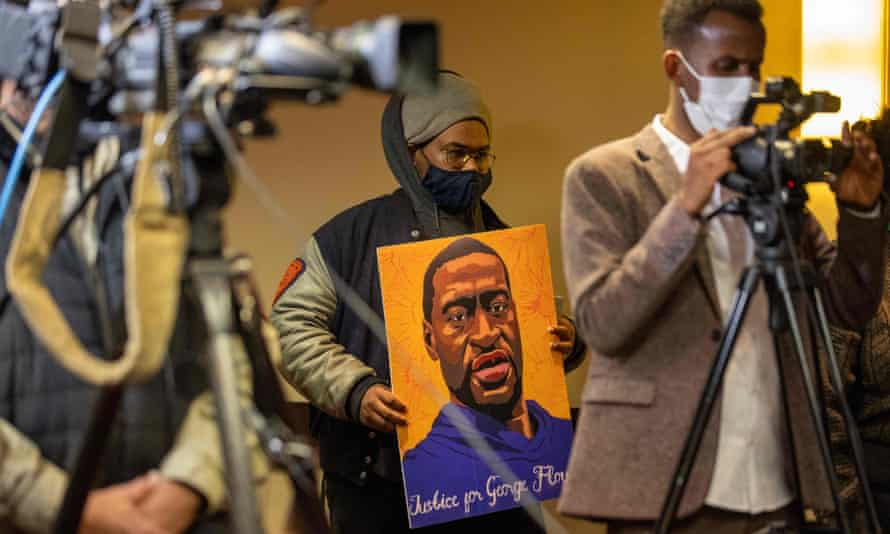 A man holds a portrait of George Floyd during press conference on the third day jury selection at the trial of Derek Chauvin on Wednesday in Minneapolis, Minnesota.