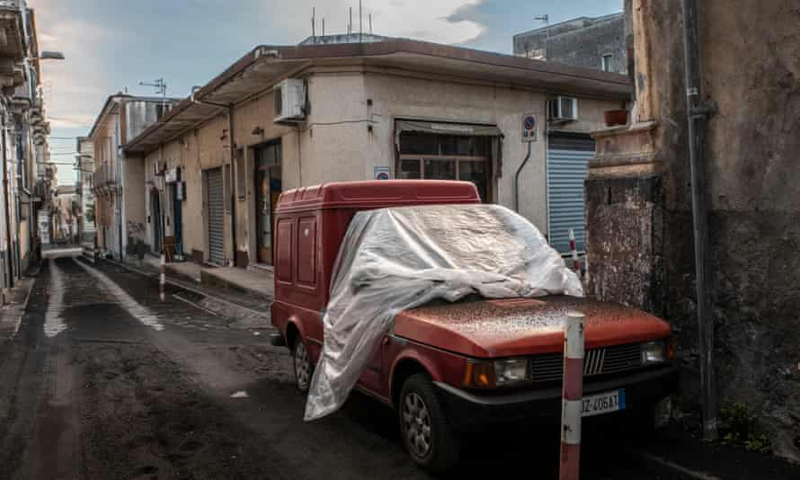 A car covered by the volcanic ash from Etna. Car owners in Giarre have to cover them with plastic sheets to protect them.