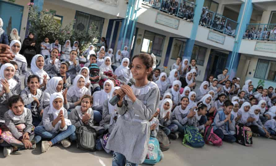 Palestinian students listen to a concert by the Edward Said National Conservatory of Music as part of the sea and freedom festival at Beit Hanoun secondary school in Gaza City.