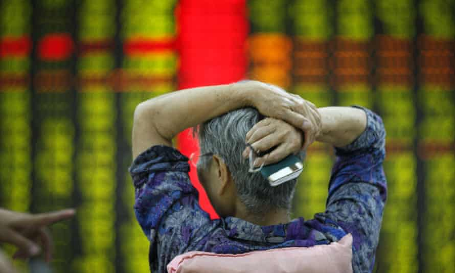 An investor watches market returns at a stock exchange hall on 27 July in Tai an, China.