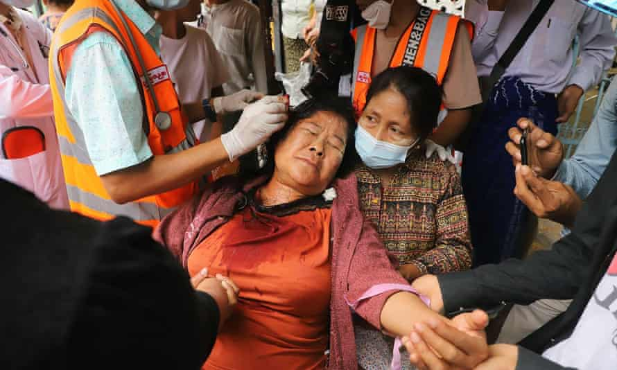 A protester is treated by medical workers after being beaten by security forces during a demonstration against the military coup in Mandalay on 20 February.