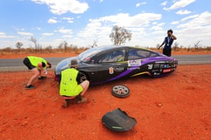 Team members change a tyre on the Sunswift car Violet from Australia as it competes in the cruiser class near Stuarts Well Roadhouse in Alice Springs