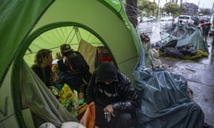 People huddle inside a tent to stay warm at a homeless encampment in Los Angeles.
