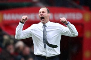 Interim Everton manager, Duncan Ferguson, who wore only a shirt in the pouring rain, celebrates after his team scored against Manchester United. The match ended 1-1.