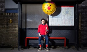 Simon Amstell sitting in a bus shelter with a balloon