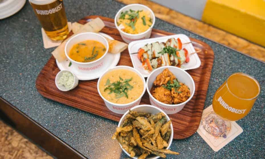 Array of food and drink, on a tray, in a picture taken from above, at Bundoust in Leeds. The eatery is a vegetarian and vegan specialist.