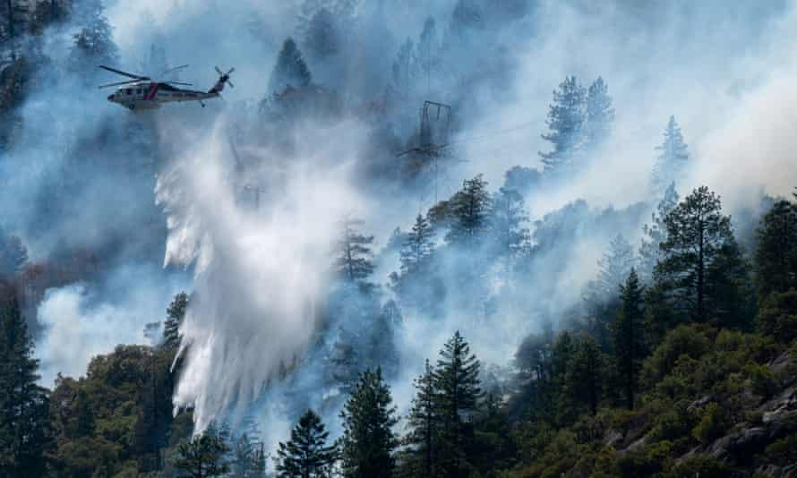 Helicopters drop water to battle the Dixie fire in Plumas county, California.