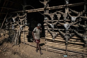 A man walking in front of his house decorated with gayal horns in Satpalaw Shaung village