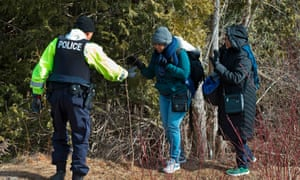 Two women from Sudan are helped by the Canadian police at the US-Canada border in February. They were arrested for crossing.
