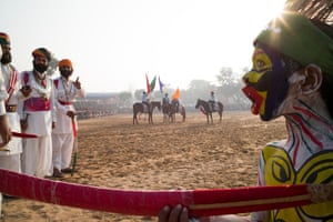 Daytime in bright sunshine, participants at the Pushkar Fair on the banks of Pushkar Lake in Rajasthan take part in events. In the foreground a young performer, face covered in multi-coloured paint holds a ceremonial sword, while in the background performers on horses mill around waiting to take part.