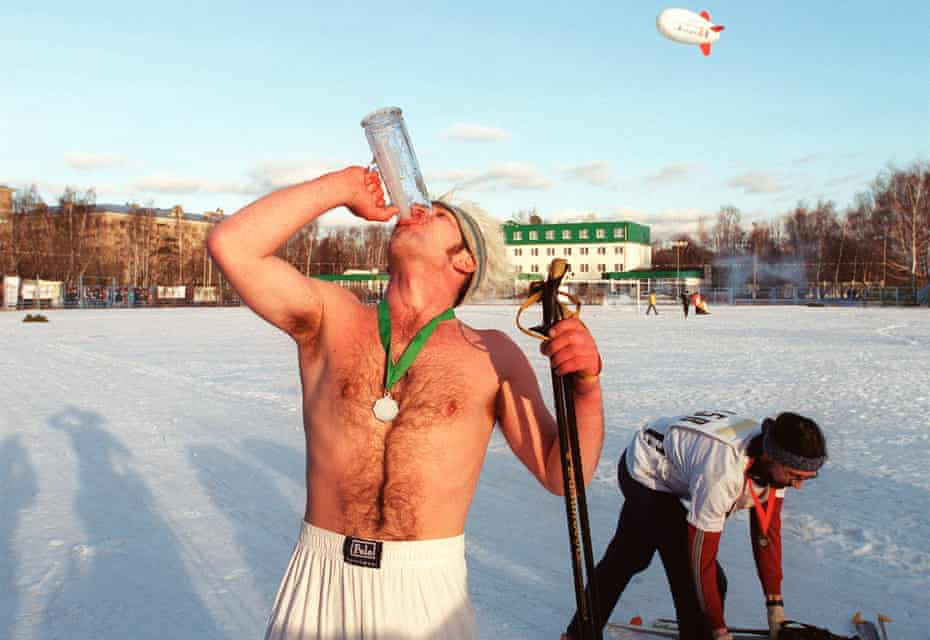 A Russian man drinks beer during a ski race requiring participants to drink the total of half a litre of vodka and five litres of beer over a 5km distance.