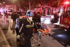Paramedics wheel an injured person on a stretcher