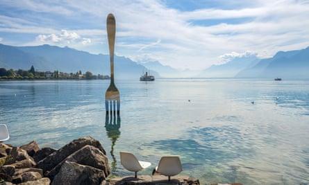 Landscape with fork sculpture in Geneva lake by artist Jean-Pierre Zaugg. Vevey, Switzerland