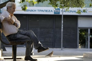 An elderly man waits outside a closed bank in Athens, Monday, June 29, 2015. Greece's five-year financial crisis took its most dramatic turn yet, with the cabinet deciding that Greek banks would remain shut for six business days and restrictions would be imposed on cash withdrawals. (AP Photo/Thanassis Stavrakis)