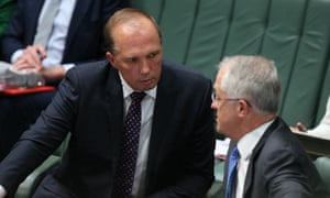 Australian immigration minister Peter Dutton talks to prime minister Malcolm Turnbull in parliament.