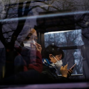People wearing masks sit in a bus during heavy traffic amid thick smog in Beijing