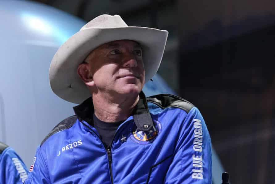 Jeff Bezos wears a Blue Origins jacket and a cowboy hat during a post launch briefing on 20 July.