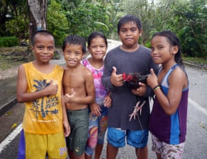 Nauruan children Breson Fritz, Nikman Garoa, Jessina Fritz, Nikalus Garoa and Zuki Bingham at Buada Lagoon with a fighting rooster