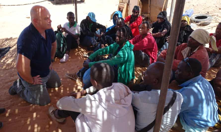 Ross Kemp with migrants waiting to be picked up