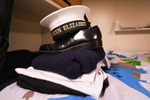 Royal Navy uniform placed on a bed onboard