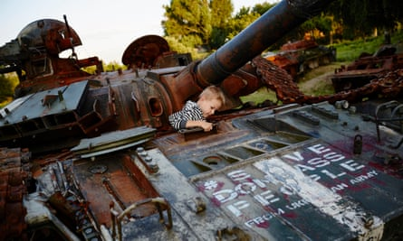 A child plays in a destroyed Ukrainian tank, scrawled with the slogan Save the Donbass people from Ukrainian army.