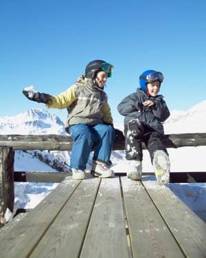 Girl (9-11) preparing to throw snowball at boy (8-10) at ski resortVal d'Isere, French Alps, France