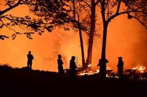 Residents look at a forest fire in El Hatillo.