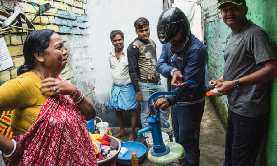 Locals use a portable hand pump to extract water from the pipes