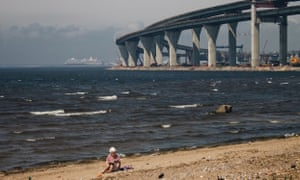 A women sits on a patch of beach and reads a book at Kanonerskiy Island, St Petersburg. In the background is the new bridge set to link the island with the mainland.