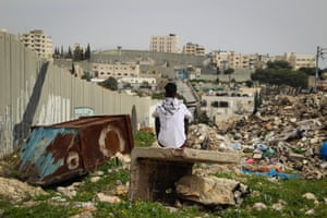 A boy looks down the length of the West Bank barrier that partially surrounds Aida camp
