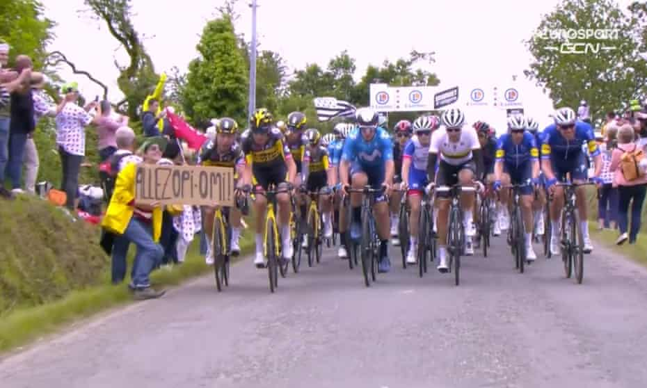 The woman holds up a sign in front of a Tour de France cyclist moments before the crash.