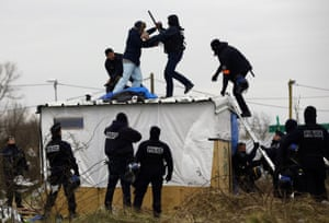 A woman fights with a police officer as she is removed from the top of a hut as police clear the Calais refugee camp on 1 March