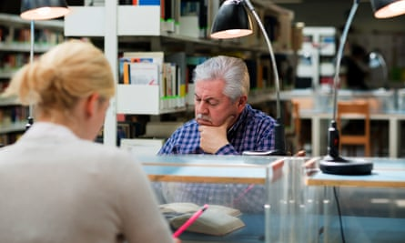 Older man studying among young college students in library