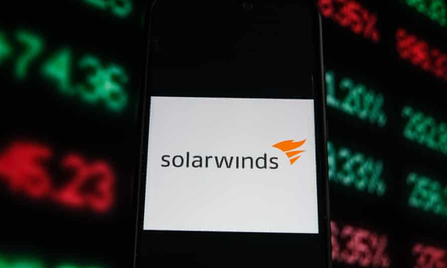 A Solarwinds logo is seen displayed on a smartphone with stock market percentages on the background.