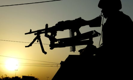 A British soldier is silhouetted as he patrols the street of Basra.