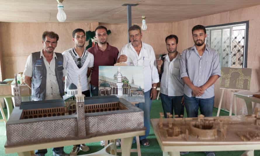 Artists in Zaatari refugee camp with their work, including a model of the Umayyad mosque in Damascus