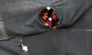 Two Syrian child refugees peer through a makeshift barrier at the Zaatari camp in Jordan.